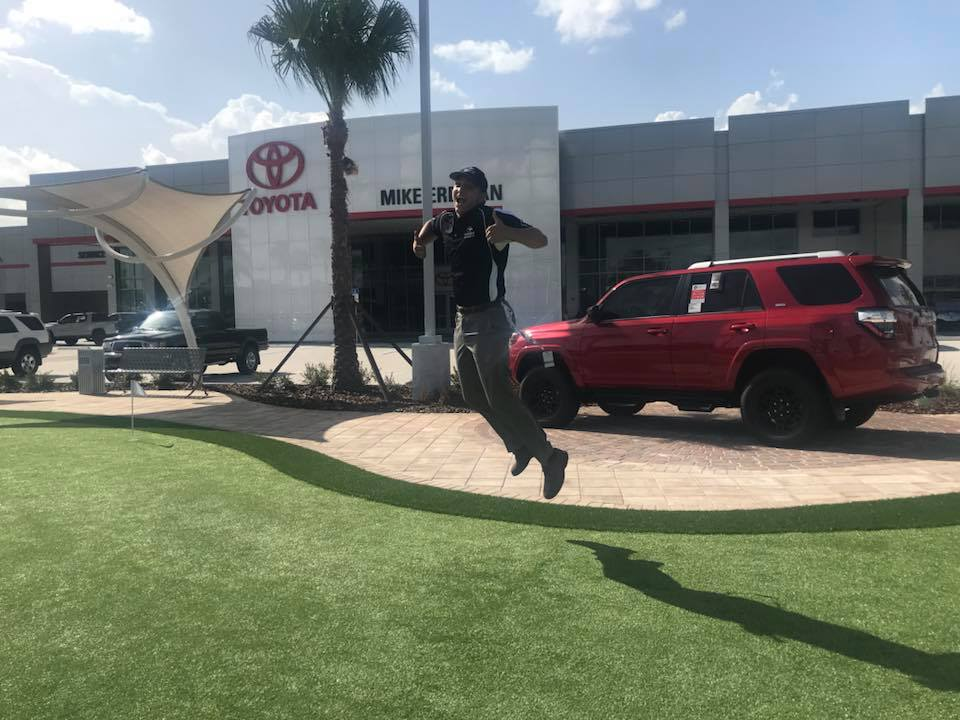 image of happy dealership worker jumping in air giving thumbs up over, over newly installed turf