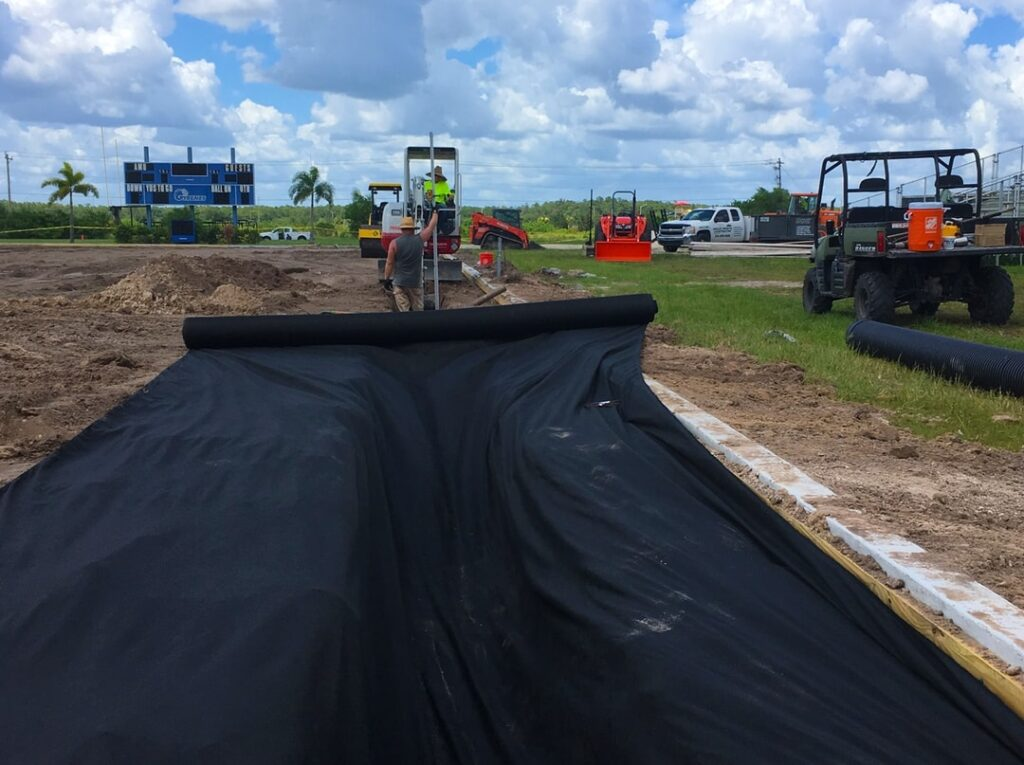 image of large tractors laying fabric for turf installation
