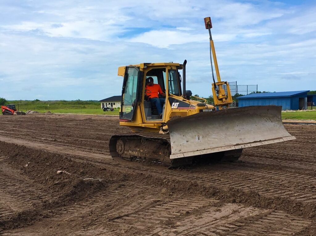 yellow bulldozer performing site work and land clearing for turf field