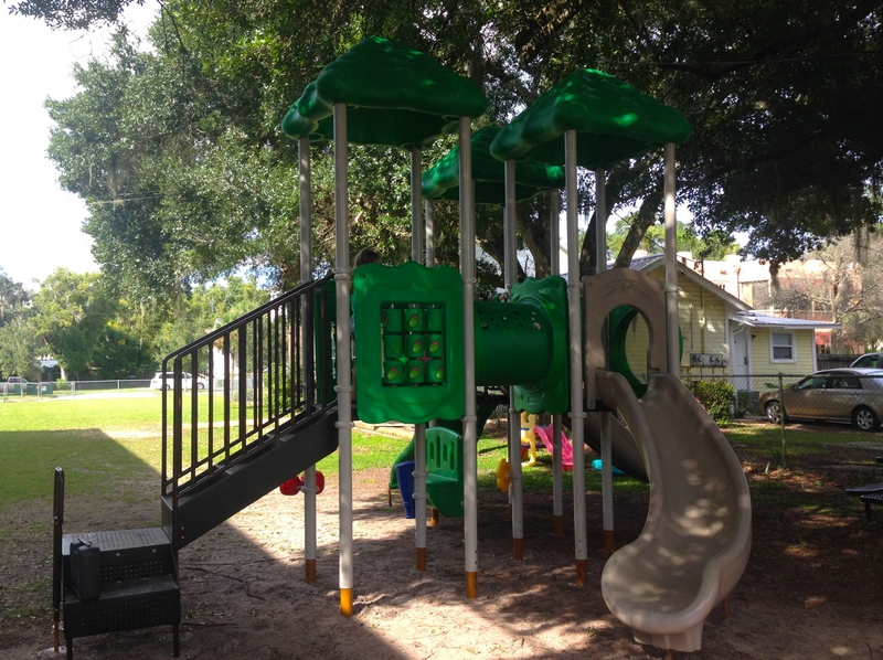 new playground installation, green tubes and tops with tan slide and steps