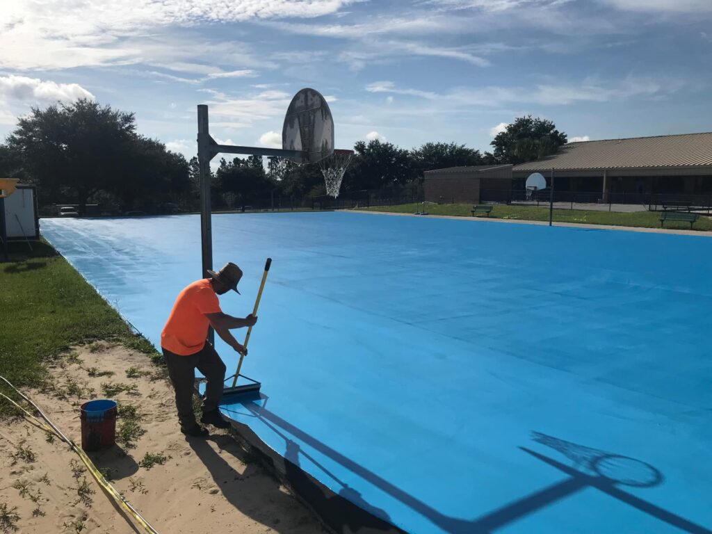 image of of man in process of resurfacing basketball court