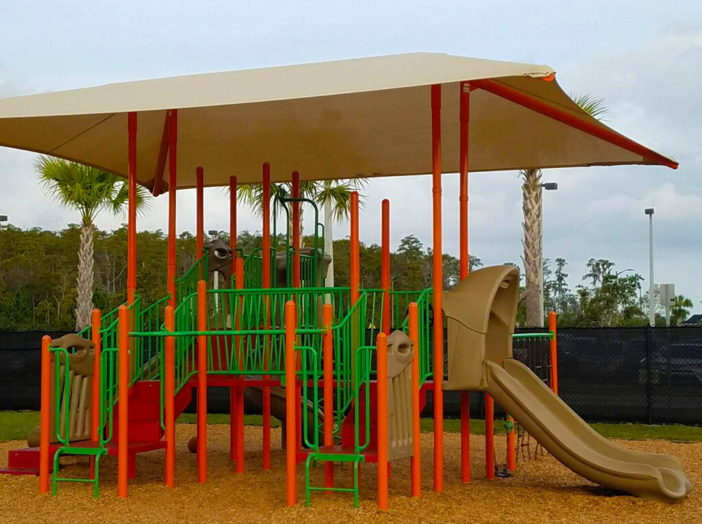 image of colorful playground with green slide and top.