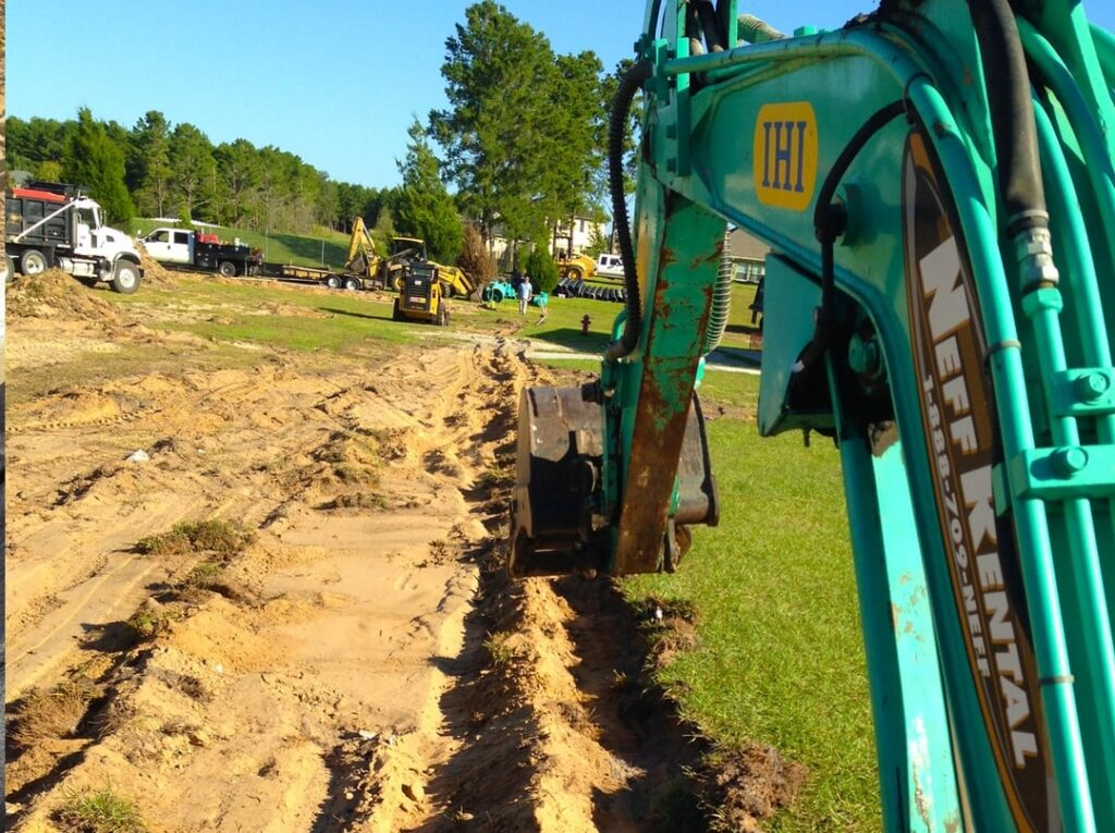 image of large green tractor removing dirt for trench in drainage field