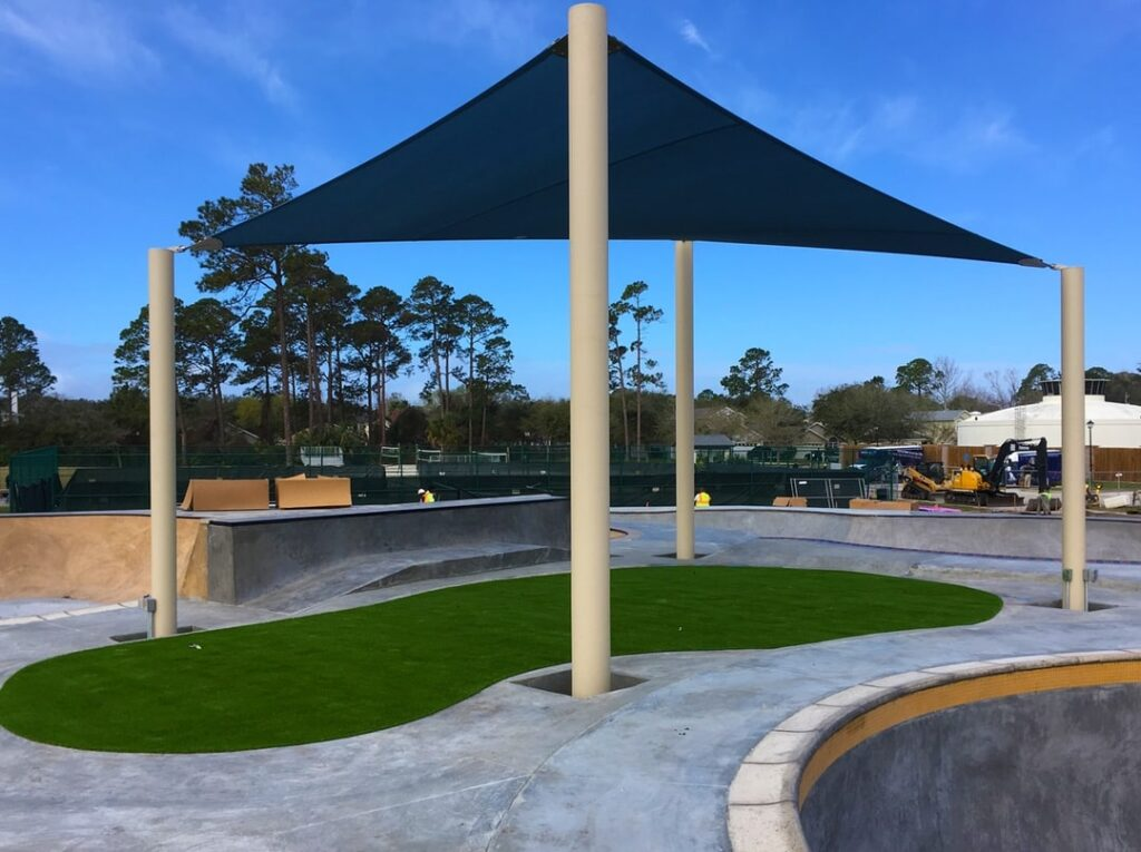 blue triangular shade erected between tall posts, covering turf area