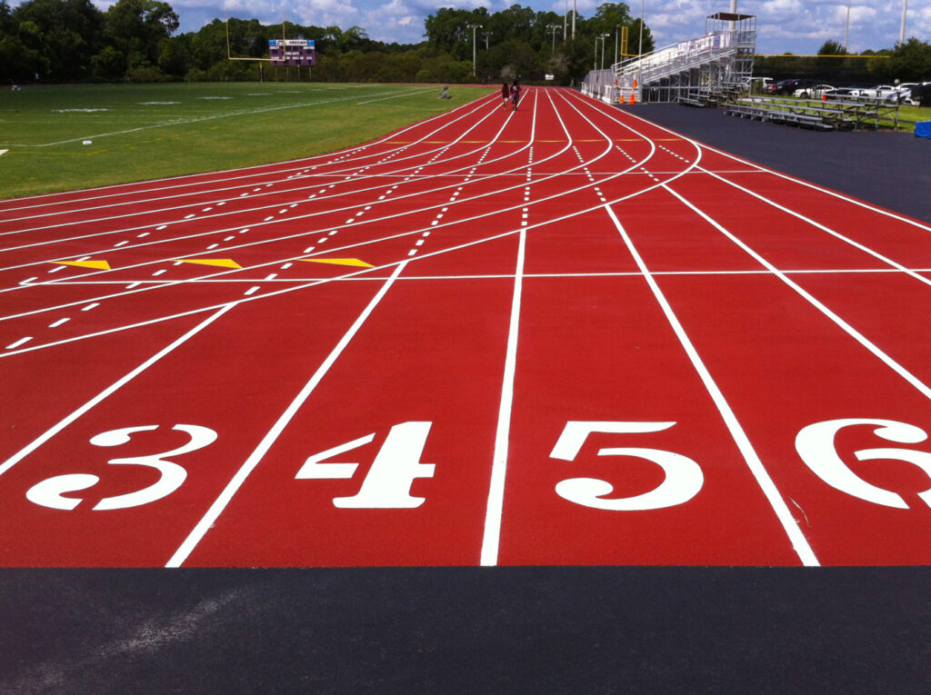 image of red running track, with white numbers painted showing lanes