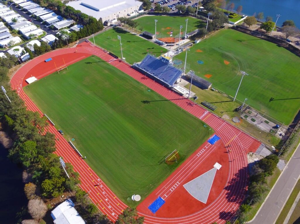 aerial image of outdoor synthetic turf football field inside of track field
