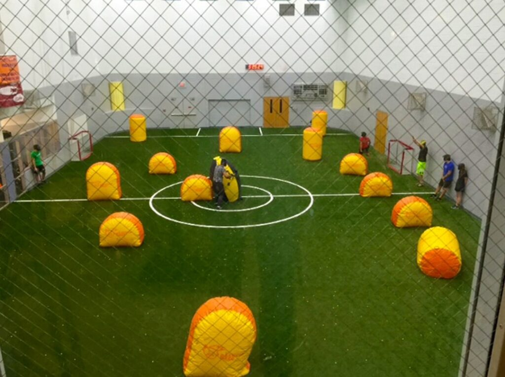 people standing on sidelines of indoor turf field with yellow inflatable game pieces