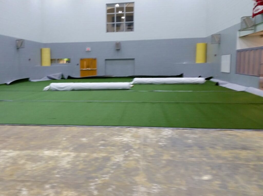 image of turf being unrolled for indoor soccer field