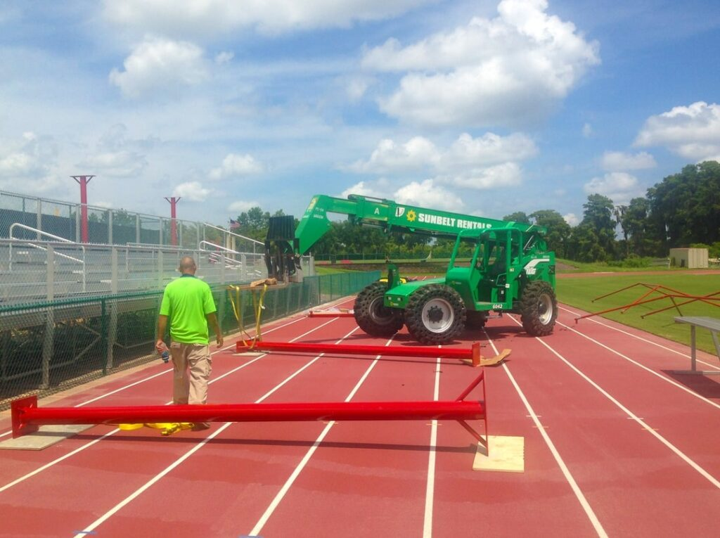 image of a man working with a crane to erect poles around running track