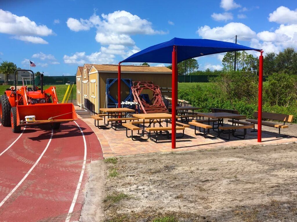 site work being done to install blue shading structure above picnic tables next to running track