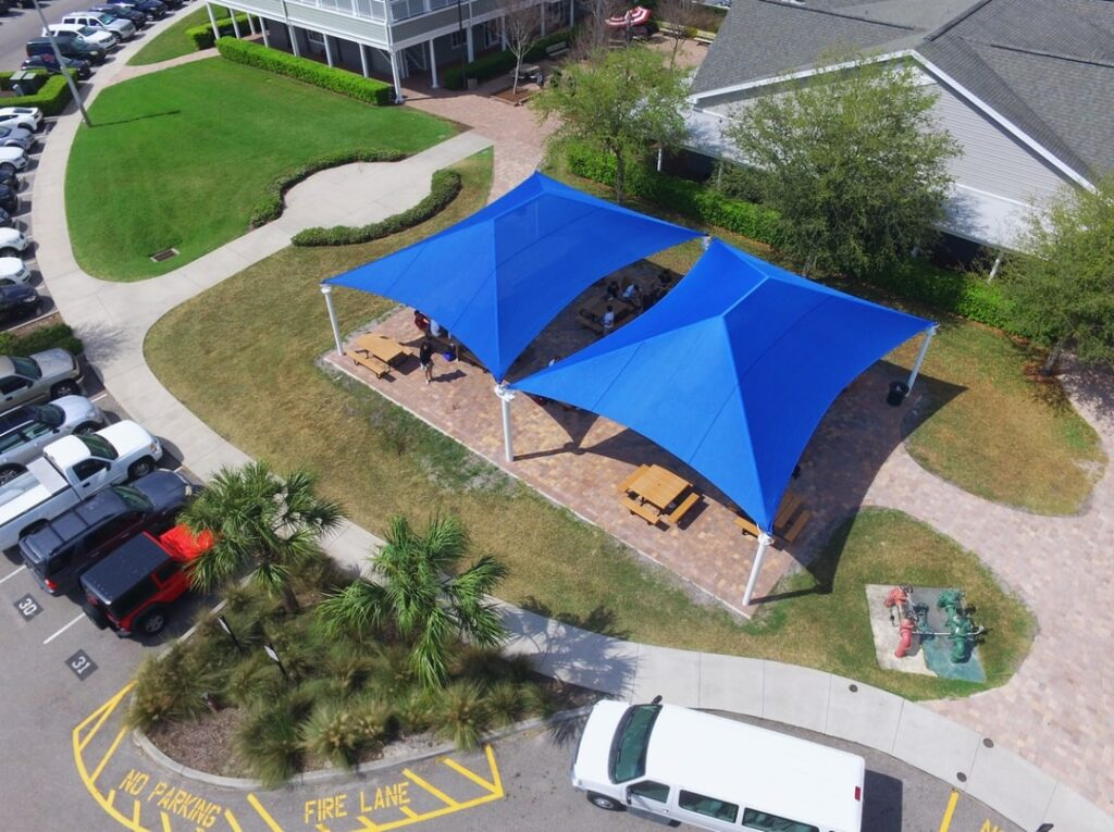 aerial image of shade structures erected over open area with picnic table seating