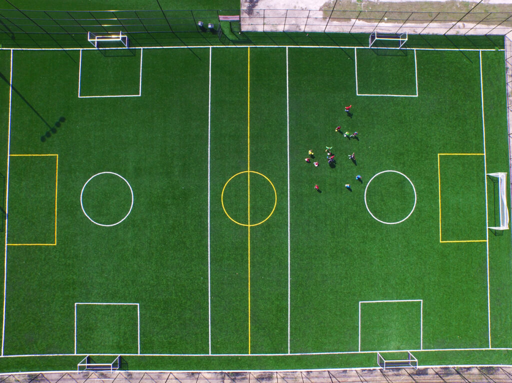aerial image of players on outdoor synthetic turf soccer field