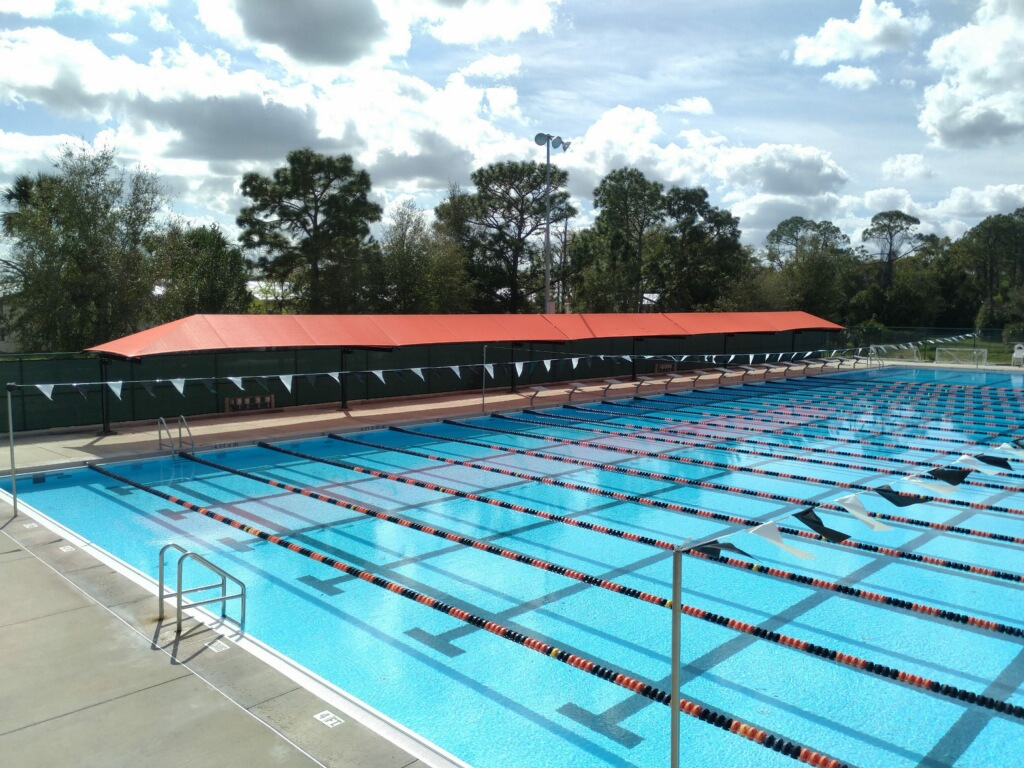 image of large blue, pool with lanes and red shading structure along pool deck