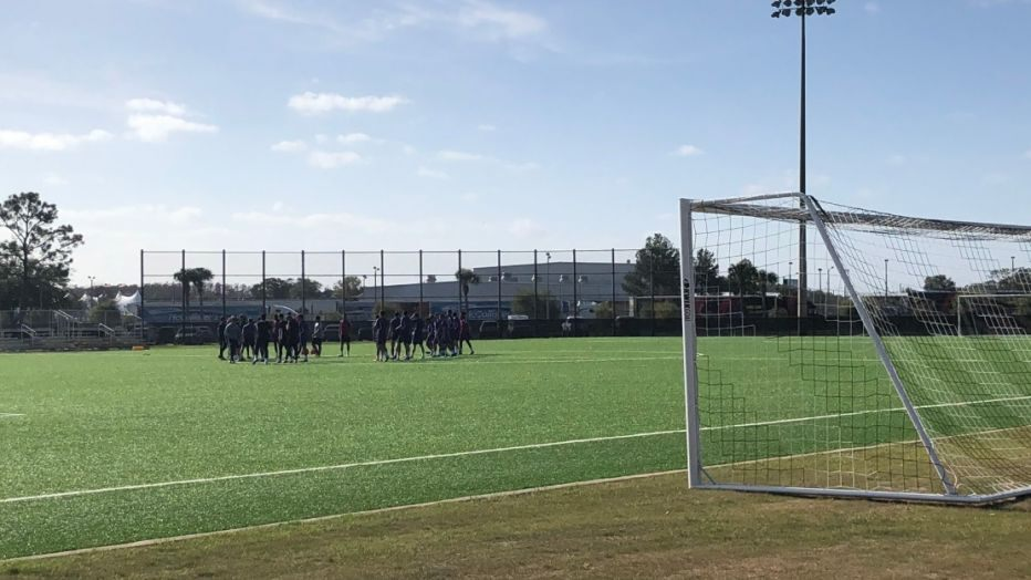 image of orlando city turf soccer field with players meeting in center of field