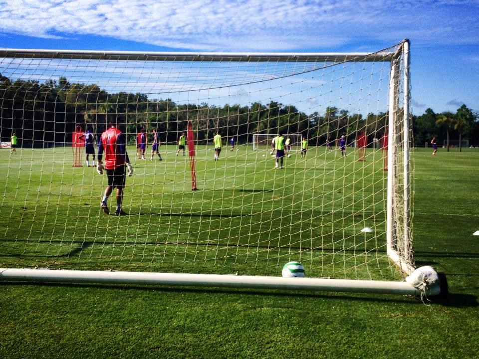 image behind the goal of orlando city soccer turf practice field with players on the field