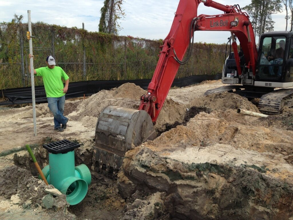 worker oversees another driving heavy equipment to complete drainage field