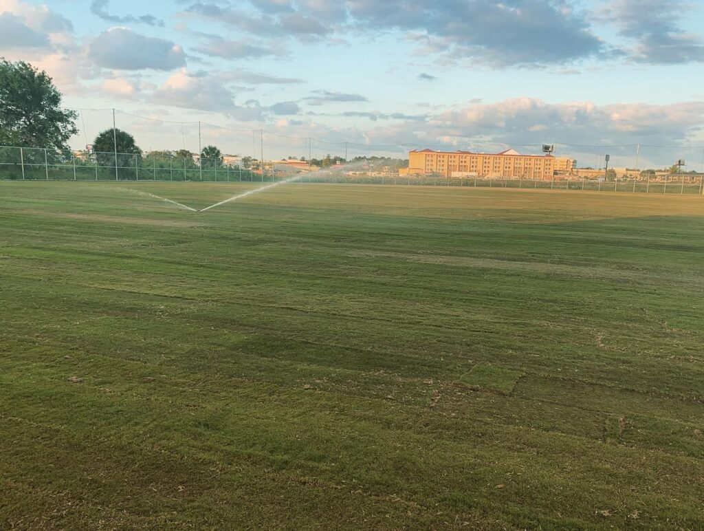 image of sprinklers spraying on recently completed natural grass soccer field, building in background