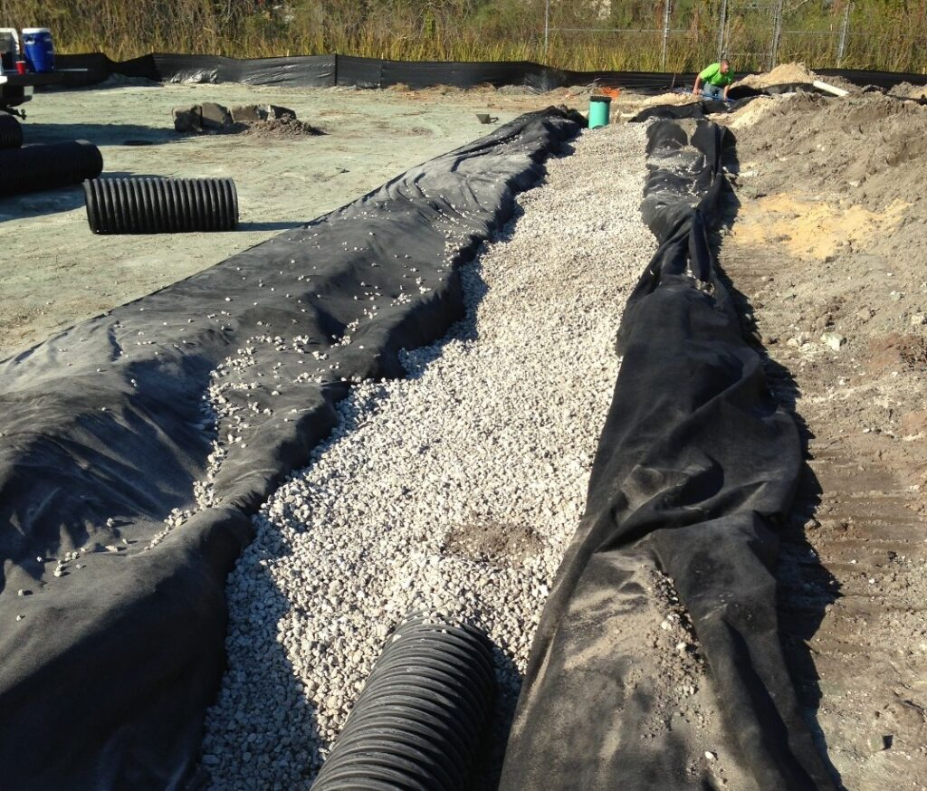 image of site work: drainage ditch with large black pipe