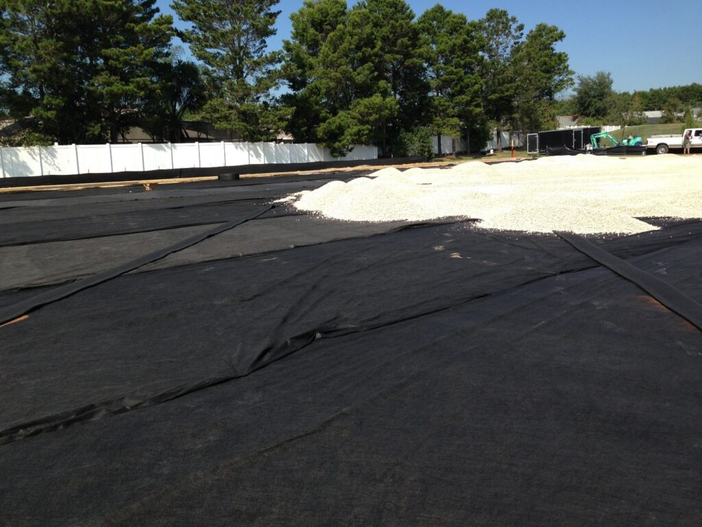 image of fabric and infill being laid for turf field during site work