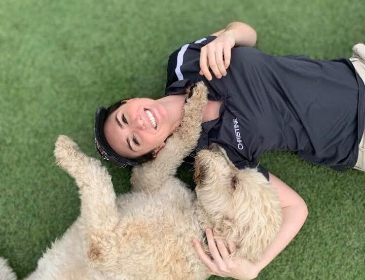 image of woman laying on floor with poodle on top of turf field