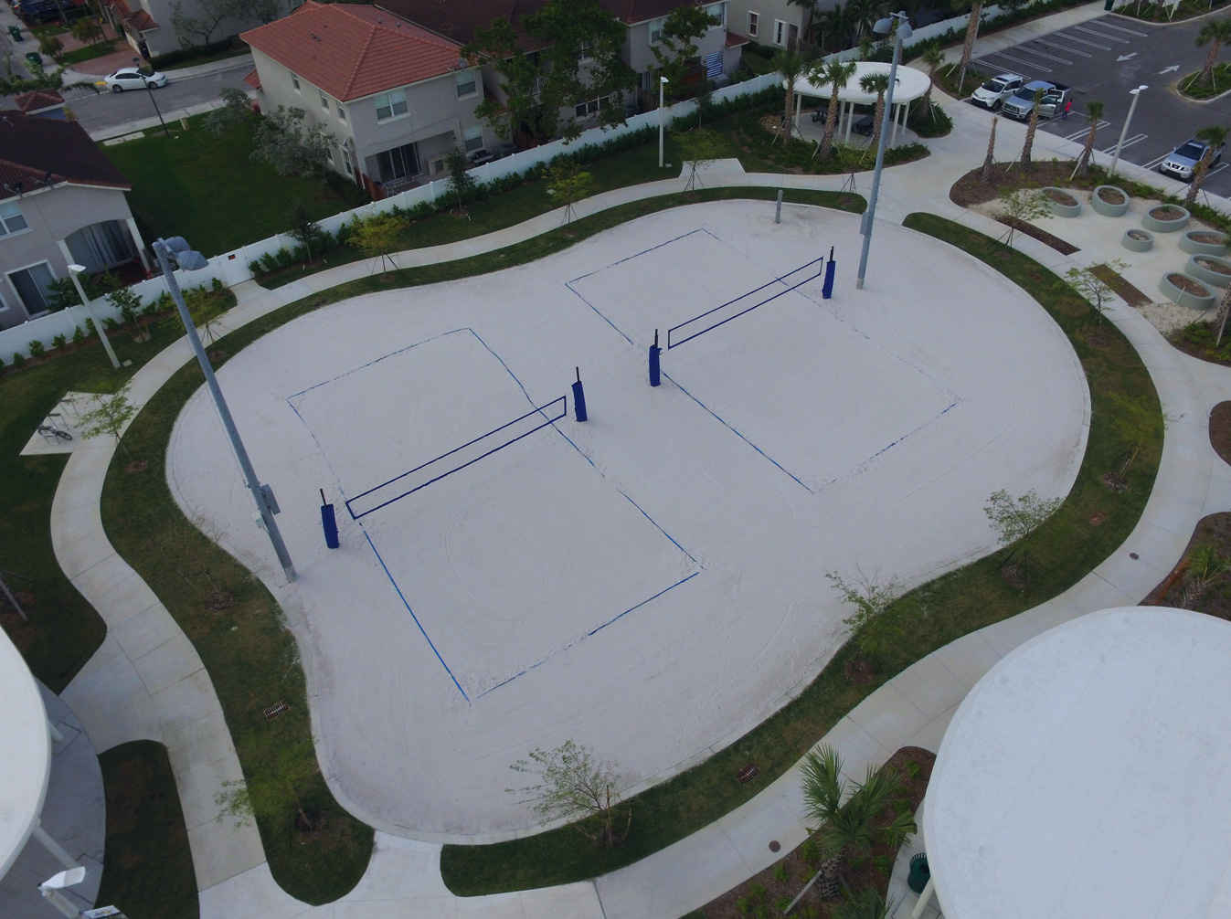 aerial image of sand volleyball court with grass surrounding border