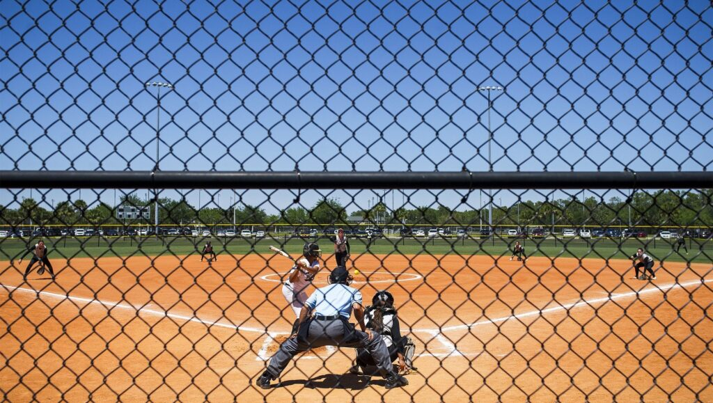 image of softball players on the field, at home plate