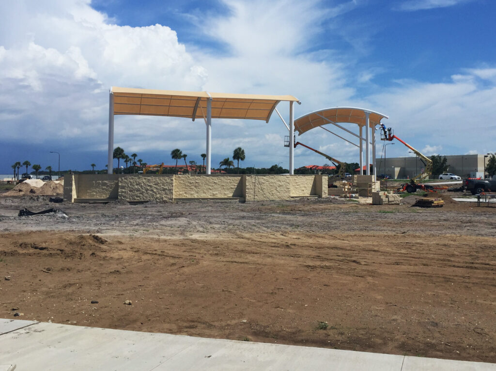 image of shade structure installation, cleared land and erecting structure with cranes