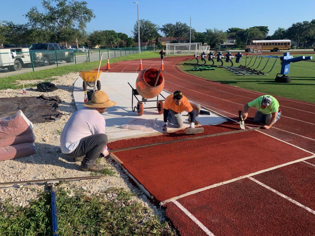 image of men working on resurfacing 400m track
