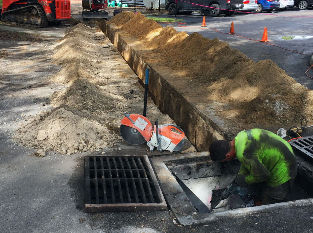 image of man working on drainage pipes for baseball field