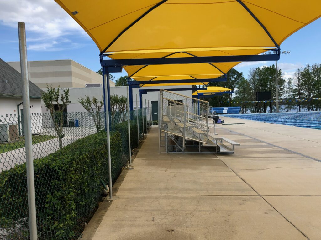 image under row of yellow shade structures along length of pool deck