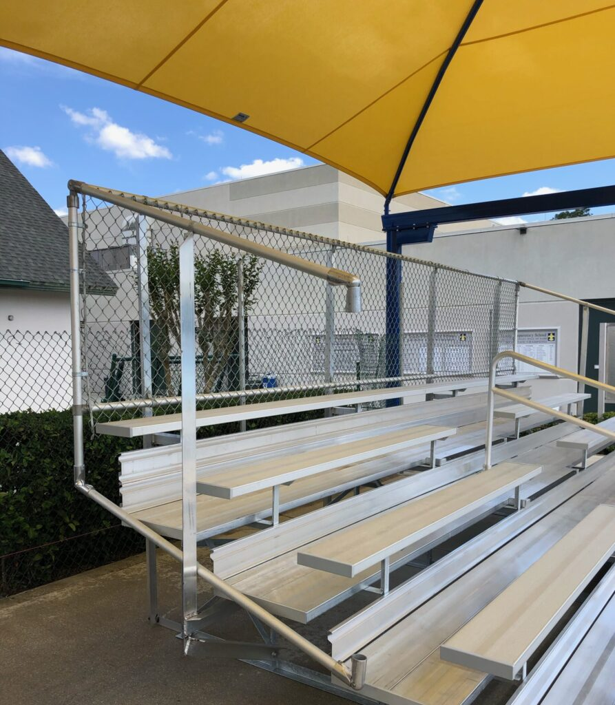 image of yellow shade structure suspended over poolside bleachers