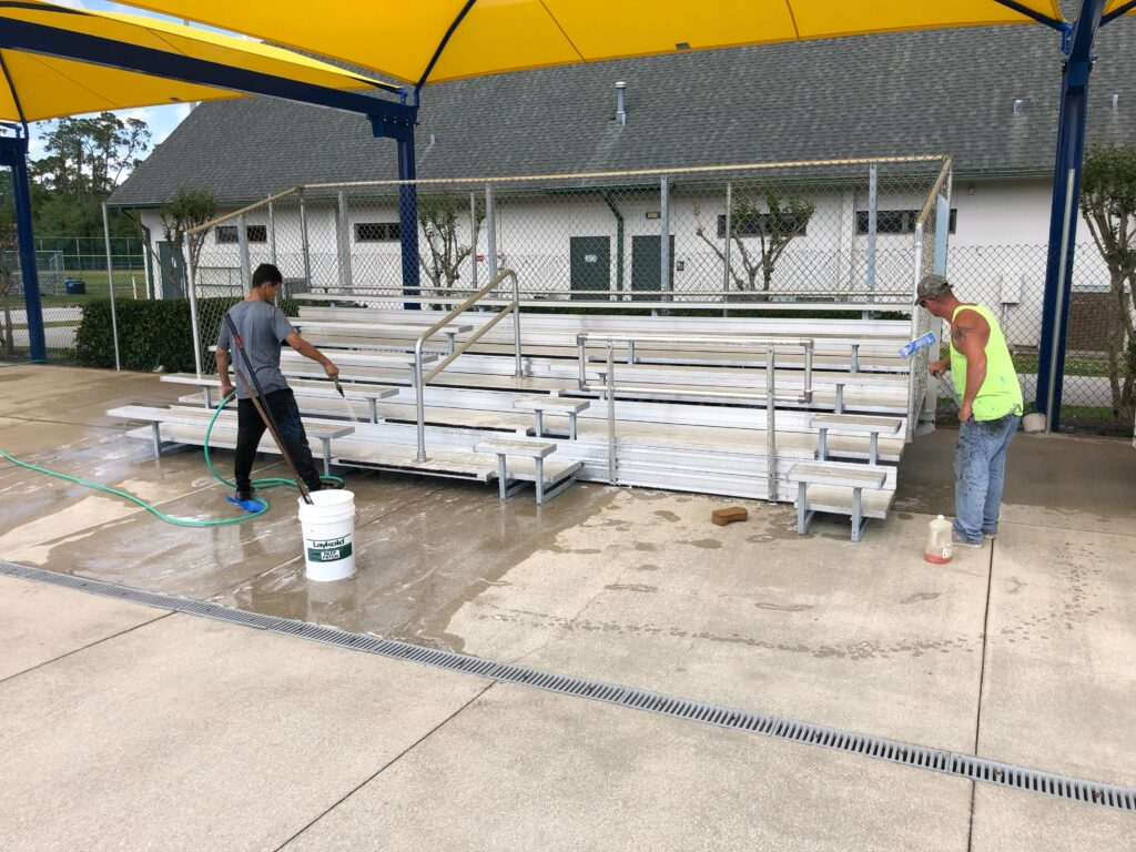 two men cleaning area in front of bleachers under new shade installation