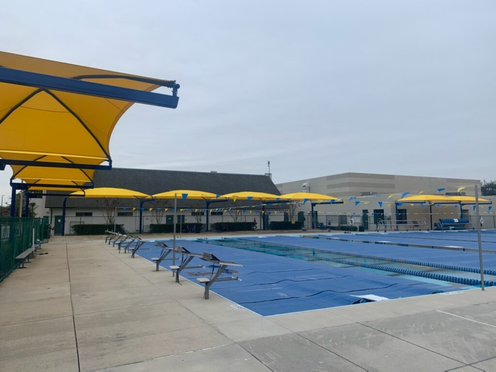 image of yellow shade structure suspended over edging of pool