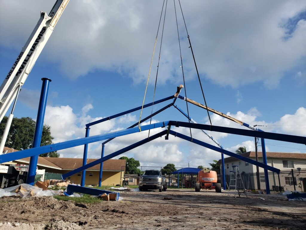 image of crane holding shade structure frame during assembly