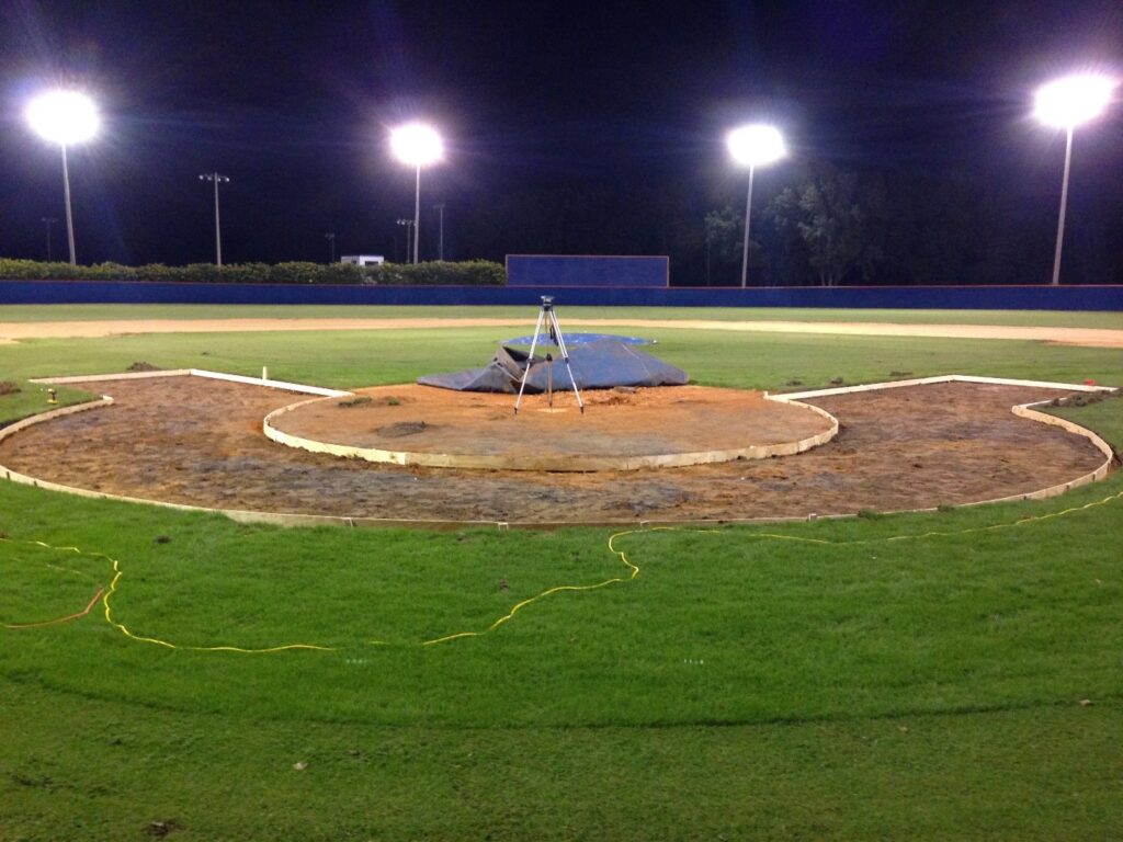 layout in ground, built of wood, for turf halo in field, night time with lights