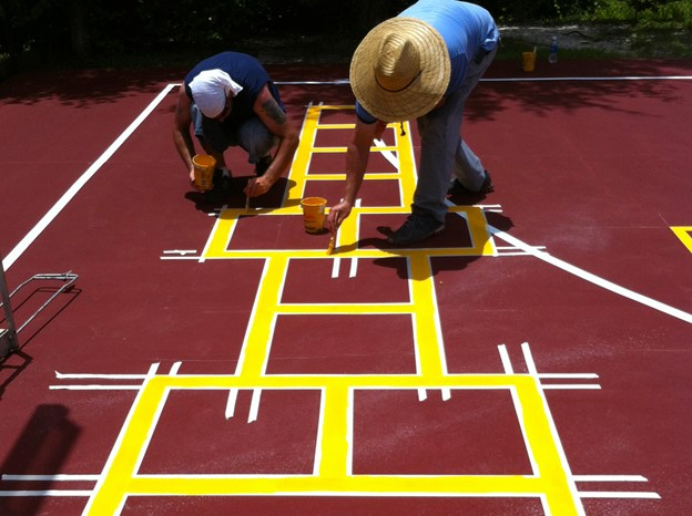 image of two workers resurfacing the basketball court