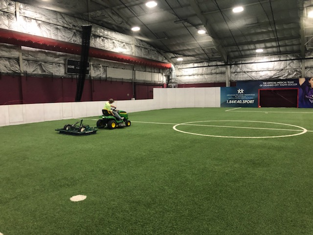man driving tractor using device to groom the synthetic turf field, he looks to his side