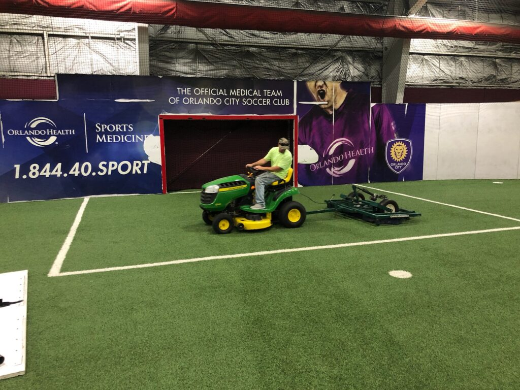 man driving tractor using device to groom the synthetic turf field, he looks behind him