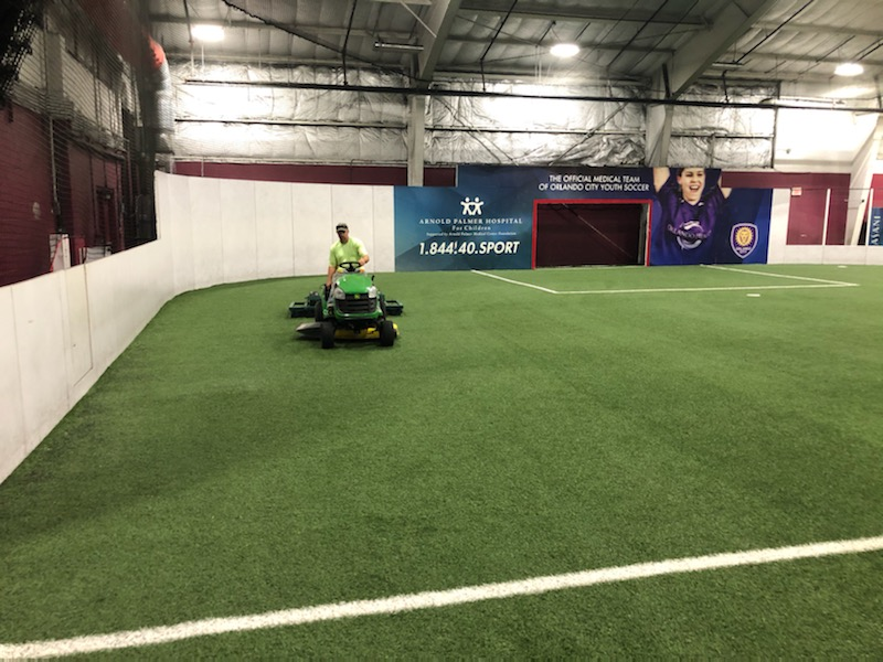 man driving tractor using device to groom the synthetic turf field, he looks ahead
