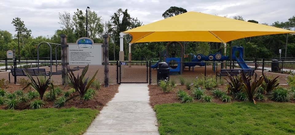 image of new shade structure, fenced in with fresh plants and landscaping