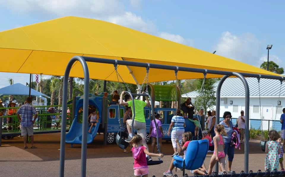 image of kids playing on swing set in front new shade structure